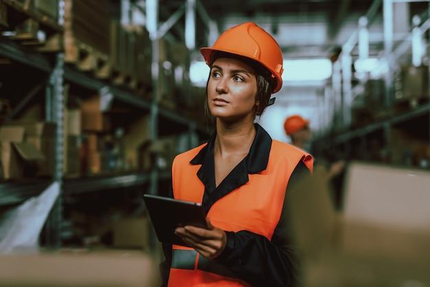 Donna in elmetto protettivo che utilizza la compressa digitale in magazzino