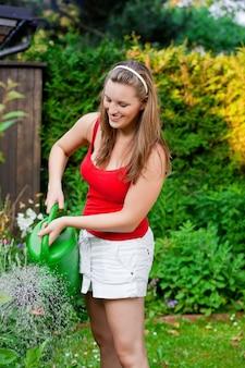 Donna in fiori d'innaffiatura del giardino