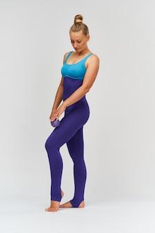 Donna in forma in abiti sportivi con palla da massaggio nelle sue mani.