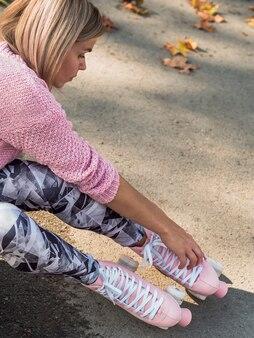 Donna in ghette che controlla i pattini di rullo