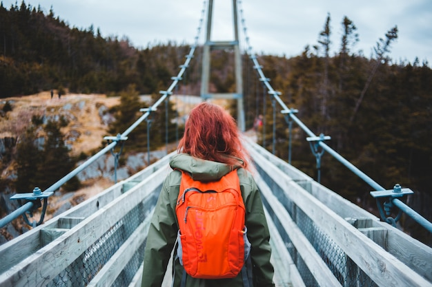 Donna in giacca arancione e jeans blu denim in piedi sul ponte durante il giorno