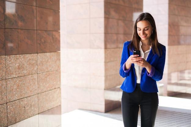 Donna in giacca blu controlla il suo cellulare