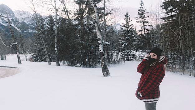 Donna in giacca calda su sfondo di albero di pino