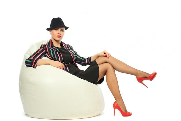 Donna in giacca e cappello eterogeneo che si siede sulla poltrona