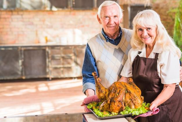 Donna in grembiule con prosciutto cotto sul piatto vicino all'uomo