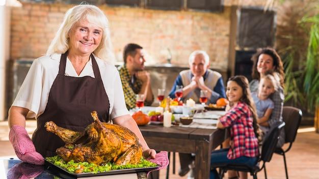 Donna in grembiule tenendo il vassoio con prosciutto arrosto