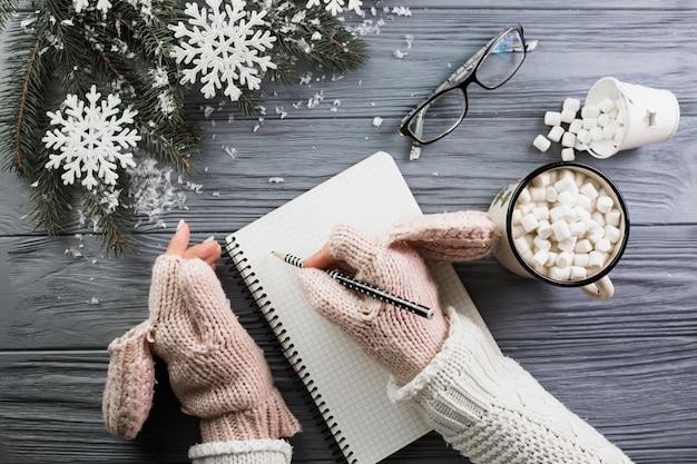 Donna in guanti che scrive in taccuino vicino alla tazza con marshmallow e occhiali