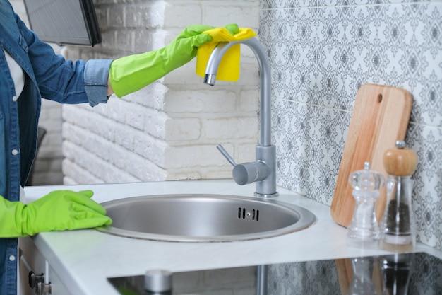 Donna in guanti con lo straccio che pulisce la cucina