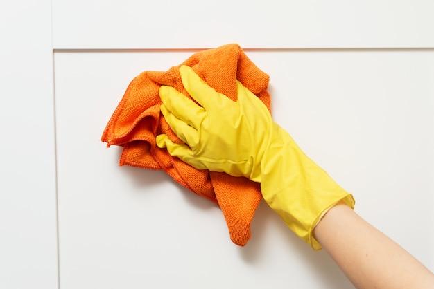Donna in guanti protettivi pulizia armadio da cucina. un primo piano di come una donna lava l'armadio