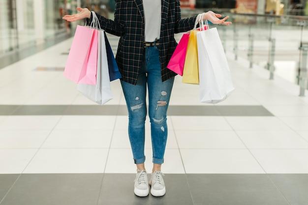 Donna in jeans che tengono i sacchetti della spesa