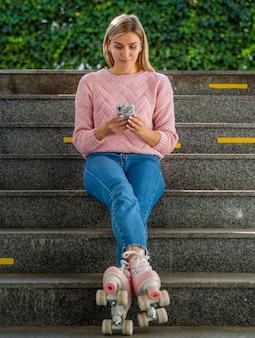 Donna in jeans e pattini a rotelle che esaminano smartphone