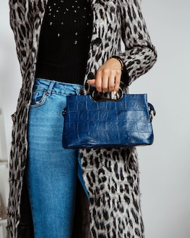 Donna in jeans, top nero e cardigan stampa leopardo con borsa blu navy