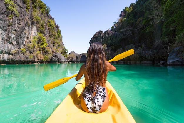 Donna in kayak nella piccola laguna di el nido, palawan, filippine - blogger di viaggio che esplora i migliori luoghi del sud-est asiatico