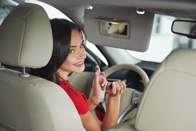 Donna in macchina coperta guardando i passeggeri nel sedile posteriore. tassista