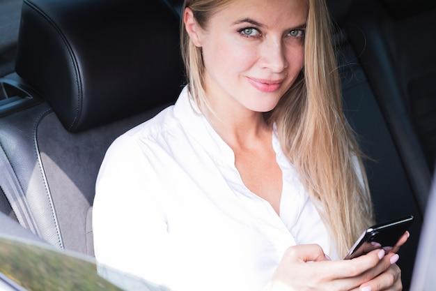 Donna in macchina e guardando la fotocamera