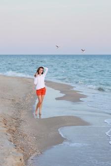 Donna in maglietta bianca e pantaloncini rossi in piedi vicino al mare su una spiaggia.