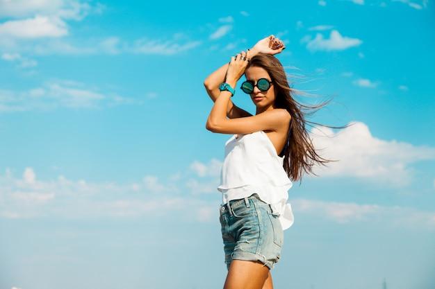 Donna in maglietta bianca ed occhiali da sole alla moda che posano sulla spiaggia. cielo blu.