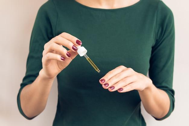 Donna in maglietta verde e manicure marrone rossiccio applicando olio per le unghie dalla pipetta