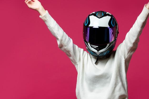 Donna in maglione bianco con casco da motociclista