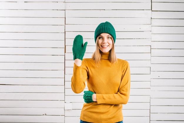 Donna in maglione che mostra gesto di saluto