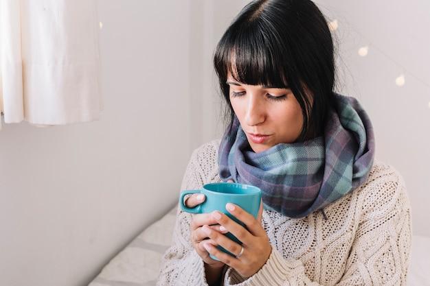 Donna in maglione che soffia sulla tazza