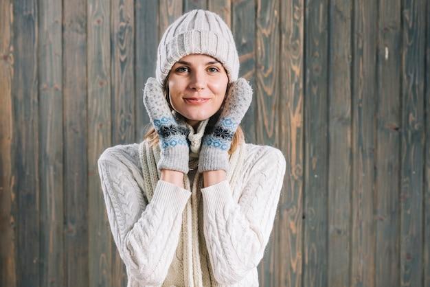 Donna in maglione che tiene le mani sulle guance