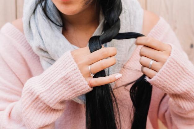 Donna in maglione intrecciare i capelli