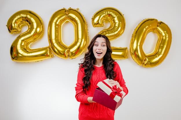 Donna in maglione rosso che apre regalo di natale davanti ai palloni del nuovo anno 2020