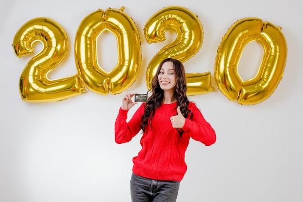 Donna in maglione rosso che tiene la carta di credito del modello davanti ai palloni del nuovo anno 2020