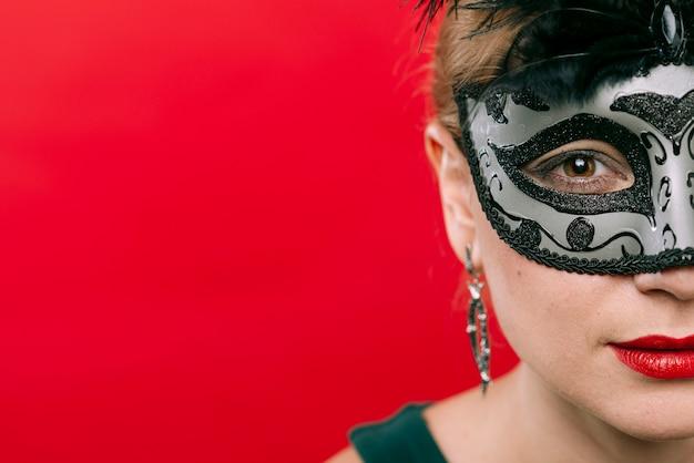 Donna in maschera di carnevale grigio con piume