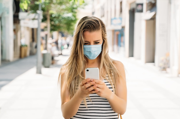Donna in maschera in città usando il suo telefono cellulare durante la pandemia di coronavirus