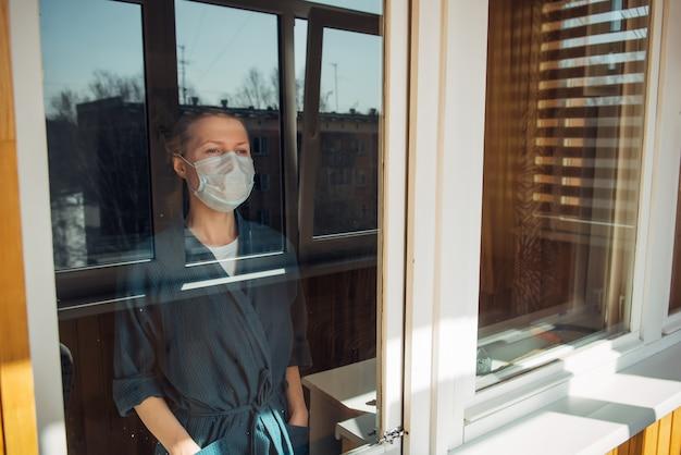 Donna in maschera medica guarda fuori dalla finestra