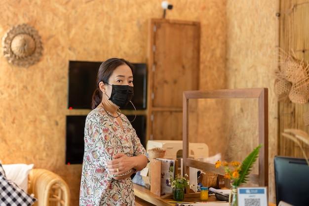 Donna in maschera medica il check-in alla reception dell'hotel
