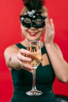 Donna in maschera nera che tiene il bicchiere di champagne