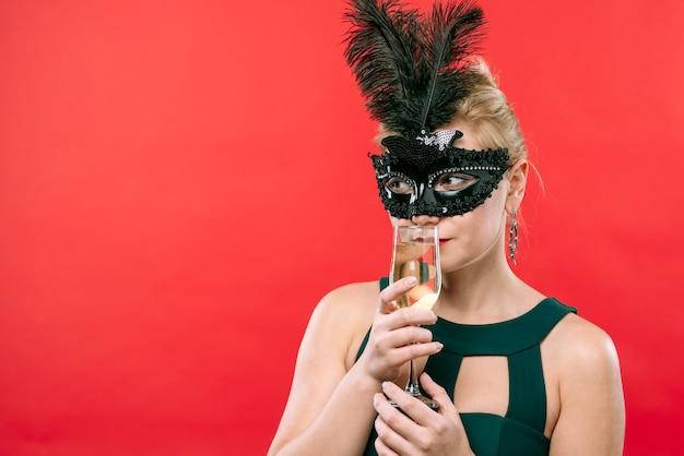 Donna in maschera nera con bicchiere di champagne
