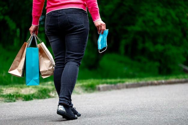 Donna in maschera protettiva con prodotti dopo lo shopping. una passeggiata nel parco dopo la quarantena