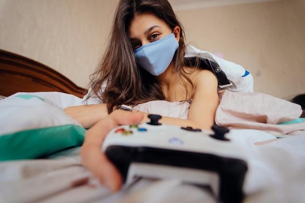 Donna in maschera protettiva sdraiata a letto e in possesso di controller