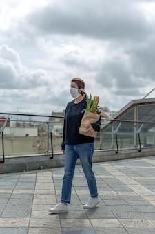 Donna in maschera protettiva tornando a casa con l'acquisto