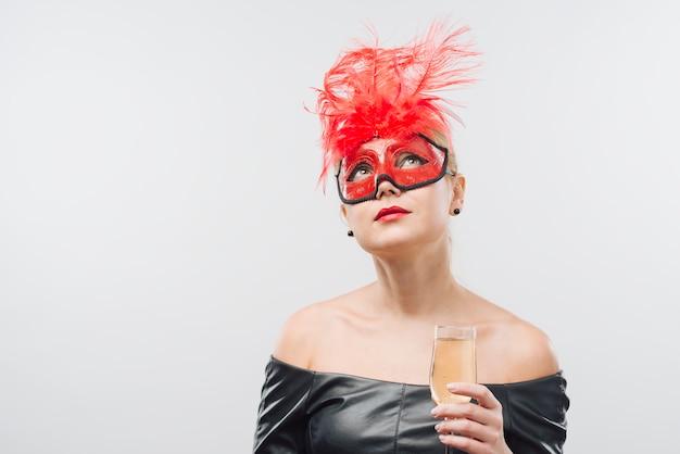 Donna in maschera rossa con bicchiere di champagne