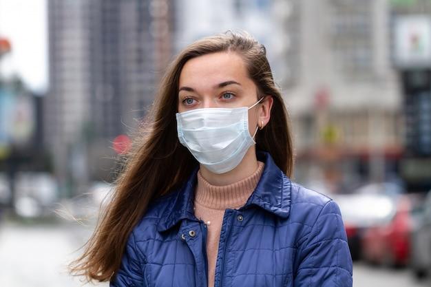 Donna in maschera sulla strada a causa dell'inquinamento atmosferico e dell'epidemia in città. protezione da virus, infezione, gas di scarico ed emissioni industriali