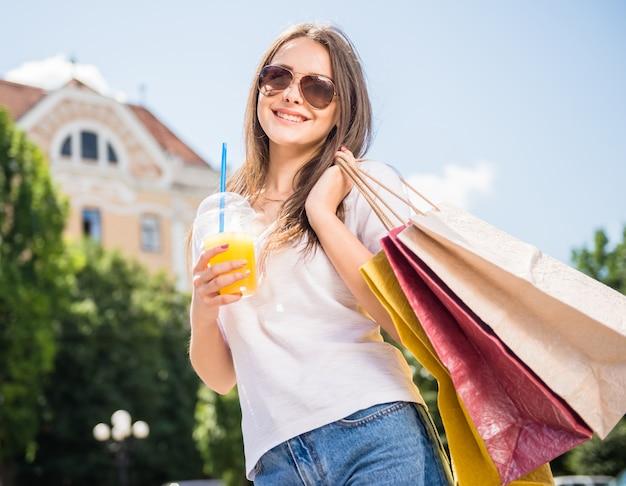 Donna in occhiali da sole che tengono i sacchetti della spesa e bicchiere di succo