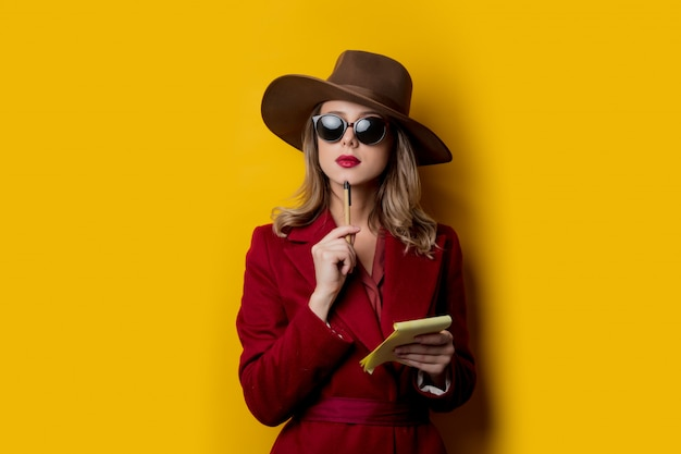 Donna in occhiali da sole con taccuino e penna