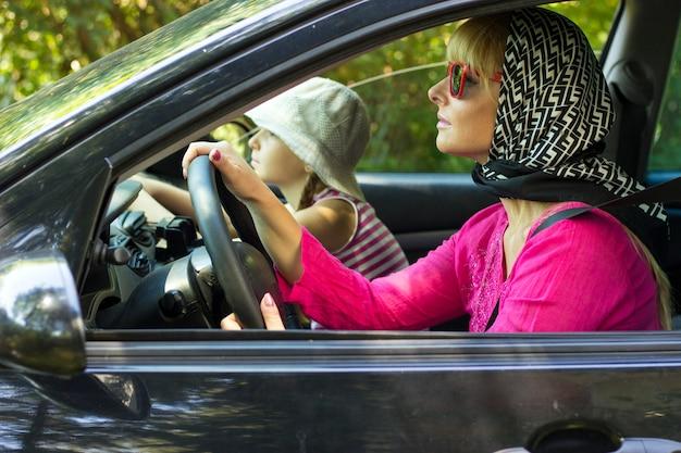 Donna in occhiali da sole rosa e rossi in macchina con la sua bella figlia