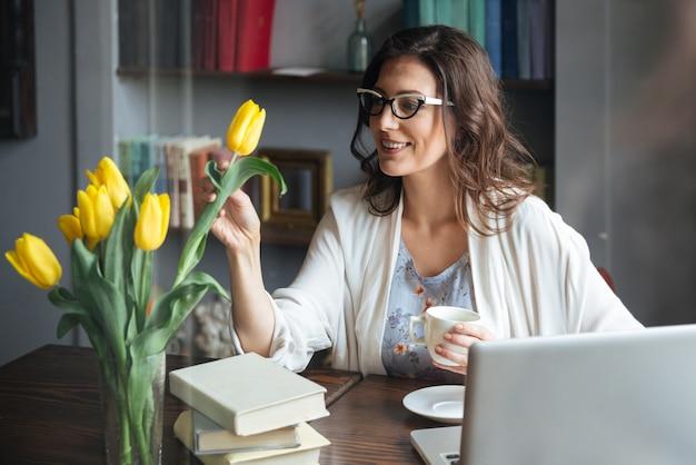 Donna in occhiali seduto al tavolo con una tazza di tè