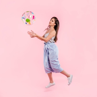 Donna in pagliaccetto che gioca con il beach ball