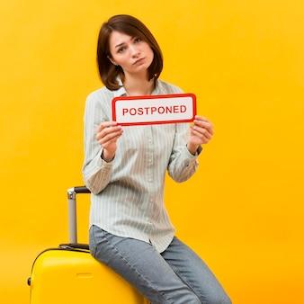 Donna in piedi accanto al suo bagaglio con in mano un cartello rinviato