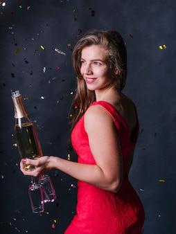Donna in piedi con bottiglia di champagne e bicchieri
