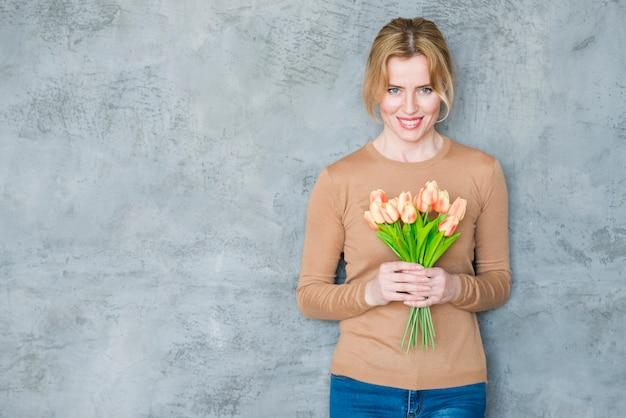 Donna in piedi con bouquet di tulipani