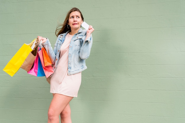 Donna in piedi con carta di credito e borse della spesa al muro verde