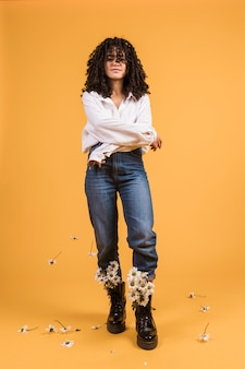 Donna in piedi con fiori in stivali e braccia incrociate